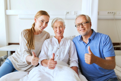 senior couple and caregiver doing thumbs up